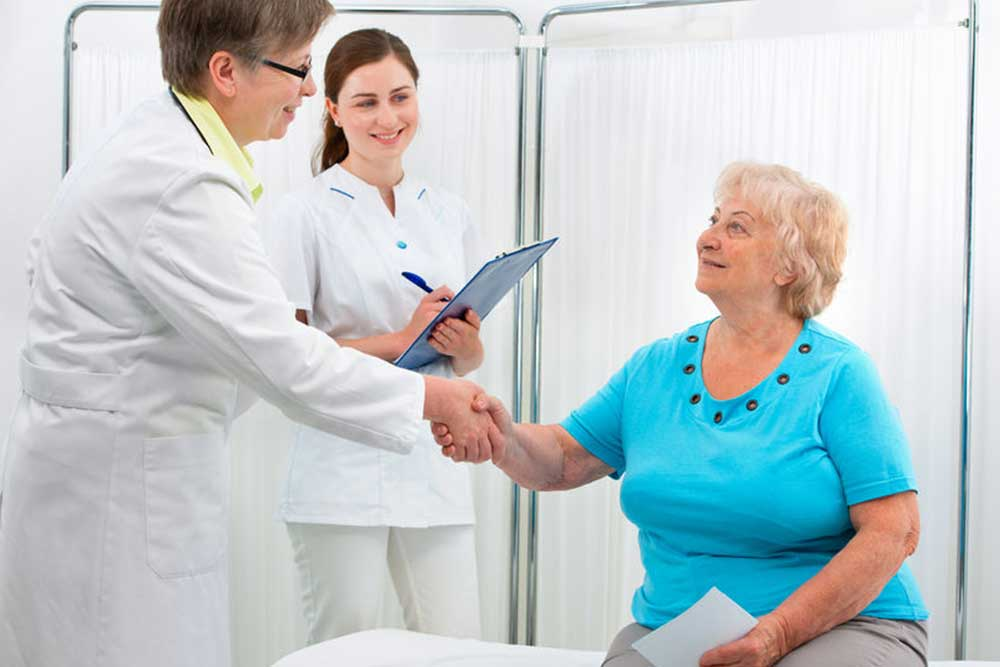 Smiling doctor at the office giving a handshake to her patient