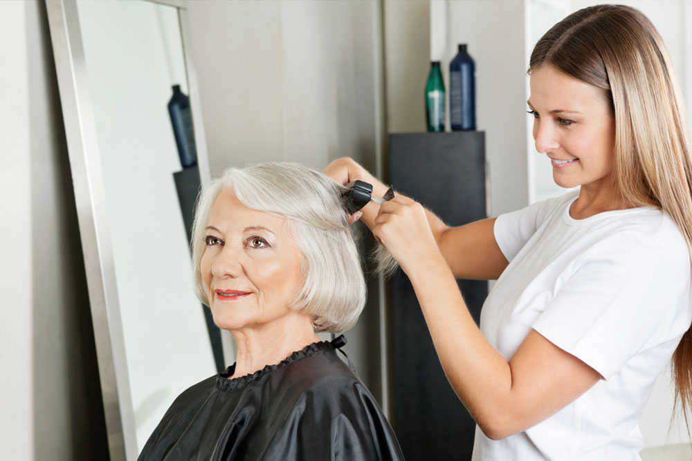 Senior woman getting her hair straightened by female hairstylist at salon
