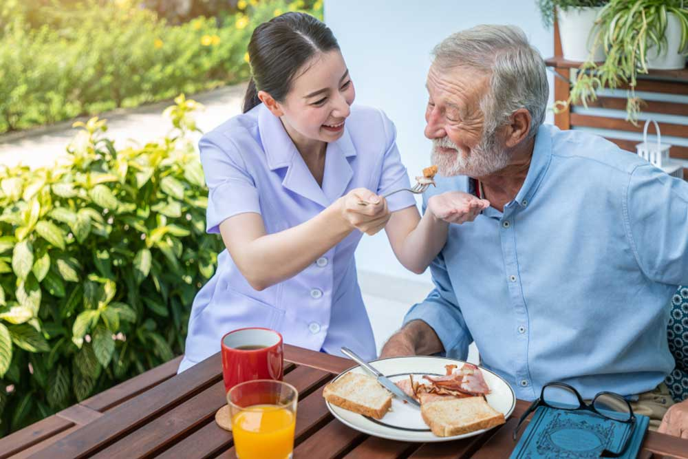 Nurse feeding elderly senior man to eat breakfast at nursing home