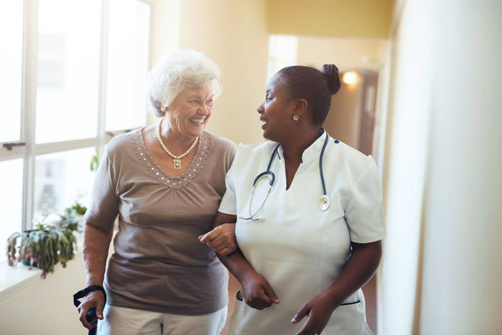 senior woman walking in the nursing home supported by a caregiver.