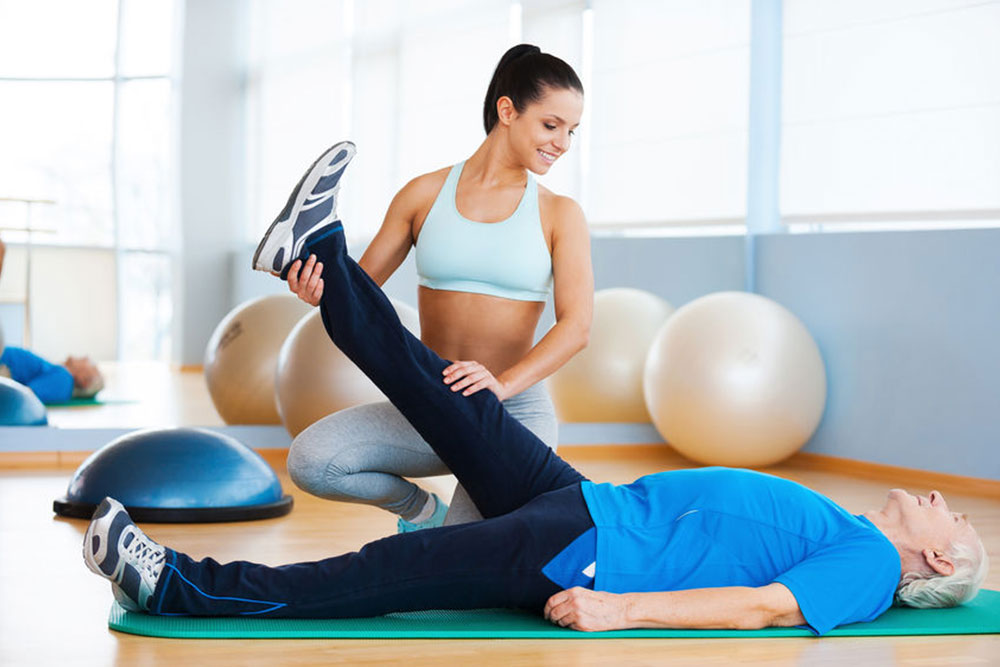 Physiotherapy. Confident female physical therapist working with senior man in health club
