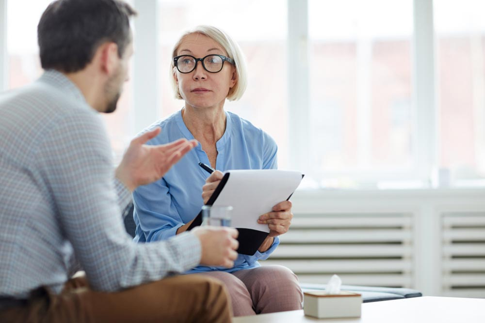Blonde mature woman making notes in document while looking at patient and listening to his story